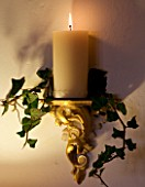 BOONSHILL FARM AT CHRISTMAS: THE DINING ROOM - LIGHTING - WALL CANDLE WRAPPED WITH IVY. DESIGNER: LISETTE PLEASANCE