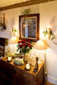 BOONSHILL FARM AT CHRISTMAS: THE DINING ROOM - LIGHTING - WALL CANDLES WRAPPED WITH IVY  MIRROR WITH MISTLETOE  SIDEBOARD WITH POINSETTIA IN CONTAINER. DESIGNER: LISETTE PLEASANCE