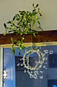 BOONSHILL FARM AT CHRISTMAS: THE DINING ROOM - MIRROR WITH MISTLETOE AND HANGING GLASS DECORATION. DESIGNER: LISETTE PLEASANCE