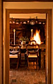 BOONSHILL FARM AT CHRISTMAS: THE DINING ROOM - TABLE WITH CHAIRS AND FIRE IN BACKGROUND. DESIGNER: LISETTE PLEASANCE