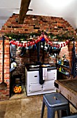 BOONSHILL FARM AT CHRISTMAS: THE KITCHEN WITH TABLE AND CHAIRS  AGA AND DECORATIONS. DESIGNER: LISETTE PLEASANCE