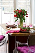 DESIGNER: CHARLOTTE ROWE  LONDON: THE DINING ROOM WITH TABLE WITH RED TULIPS IN A GLASS VASE  PINK NAPKINS AND FRESH STRAWBERRIES ON A PLATE