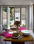 DESIGNER: CHARLOTTE ROWE  LONDON: THE DINING ROOM WITH TABLE WITH RED TULIPS IN A GLASS VASE  PINK NAPKINS AND FRESH STRAWBERRIES ON A PLATE. BEHIND IS THE GARDEN WITH OUTDOOR FIRE
