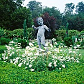 CUPID SURROUNDED BY WHITE ARGYRANTHEMUM IN THE WHITE GARDEN AT CHENIES MANOR  BUCKINGHAMSHIRE