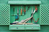 PROVENCE  FRANCE - ALTAVES. GARDENING TOOLS HANGING FROM GREEN PAINTED SHELF IN VEGETABLE GARDEN