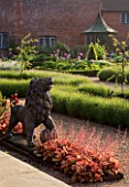 THE WALLED GARDEN AT COWDRAY  WEST SUSSEX. DESIGNER: JAN HOWARD - LION STATUE IN EARLY SUMMER BORDER WITH HEUCHERA MARMALADE AND LAVENDER HIDCOTE