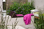 DESIGNER CHARLOTTE ROWE  LONDON: CHARLOTTE ROWES OWN GARDEN - RENDERED SEATING AREA WITH RAISED BED  CUSHIONS AND BRIGHT PINK THROW