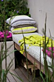 DESIGNER CHARLOTTE ROWE  LONDON: CHARLOTTE ROWES OWN GARDEN - WESTERN RED CEDAR SEAT WITH CUSHIONS AND LIME GREEN THROW