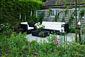 DES:CHARLOTTE ROWE LONDON.SMALL SECLUDED COUNTRY GARDEN IN JUNE WITH SOFA ARMCHAIR TABLE TRELLIS DIGITALIS PURPUREA ALBA WHITE FOXGLOVES) AND OTHER PERENNIALS WITH GLASS LANTERNS