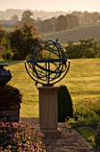 DAVID HARBER SUNDIALS: BRONZE ARMILLARY SPHERE SUNDIAL IN EVENING LIGHT WITH VIEW OF LAWN AND COUNTRYSIDE BEYOND AT PETTIFERS  OXFORDSHIRE