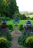 DAVID HARBER SUNDIALS: BRONZE ARMILLARY SPHERE SUNDIAL ON PATH BETWEEN STONE WALLS AND VIEW ACROSS LAWN AT PETTIFERS  OXFORDSHIRE. FORMAL GARDEN