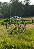 DAVID HARBER SUNDIALS: NUAGE SPHERICAL STAINLESS STEEL METAL SCULPTURE IN THE MEADOW AT PETTIFERS GARDEN  OXFORDSHIRE