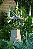DAVID HARBER SUNDIALS: STAINLESS STEEL ARMILLARY SPHERE SUNDIAL ON PLINTH WITH WHITE FOXGLOVES