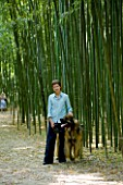 LA BAMBOUSERAIE DE PRAFRANCE  FRANCE: OWNER MURIEL NEGRE WITH HER DOG IN THE BAMBOO FOREST