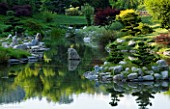 LA BAMBOUSERAIE DE PRAFRANCE  FRANCE: THE JAPANESE GARDEN - THE DRAGON VALLEY DESIGNED BY ERIK BORJA - THE LAKE WITH ROCKS AND CLOUD PRUNED CONIFERS. REFLECTION