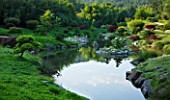 LA BAMBOUSERAIE DE PRAFRANCE  FRANCE: THE JAPANESE GARDEN - THE DRAGON VALLEY DESIGNED BY ERIK BORJA - THE LAKE WITH ROCKS AND CLOUD PRUNED CONIFERS