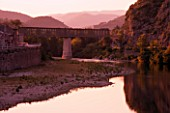 THE RIVER AND RAILWAY BRIDGE IN THE EVENING AT ANDUZE  PROVENCE  FRANCE. THE TRAIN STOPS AT THE BAMBOUSERAIE DE PRAFRANCE