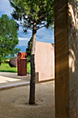 LA NORIA  FRANCE. GARDEN DESIGNED BY ARNAUD MAURIERES AND ERIC OSSART - A PINE TREE AND CONCRETE WALLS BESIDE THE GARDEN ENTRANCE