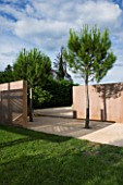 LA NORIA  FRANCE. GARDEN DESIGNED BY ARNAUD MAURIERES AND ERIC OSSART - PINE TREES AND CONCRETE WALLS BESIDE THE GARDEN ENTRANCE
