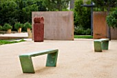 LA NORIA  FRANCE. GARDEN DESIGNED BY ARNAUD MAURIERES AND ERIC OSSART - CONCRETE WALLS AND GREEN BENCHES BESIDE THE GARDEN ENTRANCE - A PLACE TO SIT
