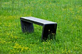 LA NORIA  FRANCE. GARDEN DESIGNED BY ARNAUD MAURIERES AND ERIC OSSART -  A BLACK CONCRETE BENCH IN THE PRAIRIE DE SCULPTURES - A PLACE TO SIT