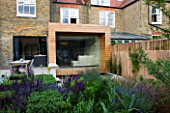 GARDEN DESIGNER: CHARLOTTE ROWE  LONDON: FORMAL TOWN/CITY GARDEN. VIEW TOWARDS HOUSE WITH GLASS & TIMBER EXTENSION AND DINING AREA