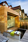 GARDEN DESIGNER: CHARLOTTE ROWE  LONDON: GLASS & TIMBER EXTENSION AND DECK/POOL WITH THROW AND CUSHIONS