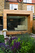GARDEN DESIGNER: CHARLOTTE ROWE  LONDON: VIEW TOWARDS HOUSE WITH GLASS & TIMBER EXTENSION FROM FORMAL TOWN/CITY GARDEN WITH PERENNIAL PLANTING