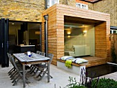 GARDEN DESIGNER: CHARLOTTE ROWE  LONDON: VIEW OF KITCHEN AND DINING AREA WITH GLASS AND TIMBER EXTENSION WITH POOL AND DECK