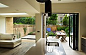 GARDEN DESIGNER: CHARLOTTE ROWE  LONDON: VIEW FROM OPEN-PLAN KITCHEN AND LIVING AREA OUT ONTO FORMAL TOWN/CITY GARDEN WITH DINING AREA AND SPLIT LEVEL DECK