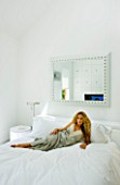 TANIA LAURIE  LONDON. TANIA RELAXES ON HER BED IN HER WHITE-THEMED BEDROOM