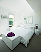 TANIA LAURIE  LONDON. WHITE BEDROOM WITH BED  BLANKET BOX AND BEDSIDE TABLE WITH VASE OF SCENTED STOCK