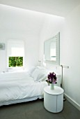 TANIA LAURIE  LONDON. WHITE BEDROOM WITH MIRROR ABOVE BED AND BEDSIDE TABLE WITH VASE OF SCENTED STOCK