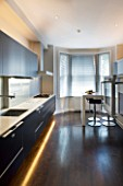 TANIA LAURIE  LONDON. CONTEMPORARY KITCHEN WITH LIGHTING  BLACK UNITS  WOODEN FLOOR AND BREAKFAST BAR