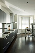 TANIA LAURIE  LONDON. CONTEMPORARY KITCHEN WITH BLACK UNITS  WOODEN FLOOR AND BREAKFAST BAR