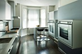 TANIA LAURIE  LONDON. CONTEMPORARY KITCHEN WITH BLACK UNITS  DOUBLE OVENS AND BREAKFAST BAR