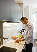 TANIA LAURIE  LONDON. TANIAS PARTNER DANIEL PREPARES LUNCH IN THEIR STYLISH  CONTEMPORARY KITCHEN