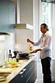TANIA LAURIE  LONDON. TANIAS PARTNER DANIEL COOKING LUNCH IN THEIR STYLISH  CONTEMPORARY KITCHEN