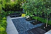 TANIA LAURIE  LONDON. SMALL CONTEMPORARY GARDEN BY CHARLOTTE ROWE. EATING/ENTERTAINING AREA WITH POLISHED GREY PEBBLES WITH OPHIOPOGON PLANTED INTO SQUARES WITH CATALPA