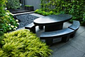 TANIA LAURIE  LONDON. SMALL CONTEMPORARY GARDEN BY CHARLOTTE ROWE WITH BLACK MARBLE OVAL TABLE AND BENCHES WITH HAKONECHLOA MACRA ALBOAUREA  HYDRANGEA AND POLISHED GREY PEBBLES