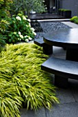 TANIA LAURIE  LONDON. SMALL CONTEMPORARY GARDEN BY CHARLOTTE ROWE WITH HAKONECHLOA MACRA ALBOAUREA BESIDE BLACK MARBLE TABLE AND BENCHES. HYDRANGEA ARBORESCENS ANNABELLE IN B/G