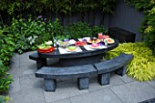 TANIA LAURIE  LONDON. LUNCH WAITING TO BE SERVED ON BLACK MARBLE TABLE AND BENCHES IN CONTEMPORARY GARDEN DESIGNED BY CHARLOTTE ROWE