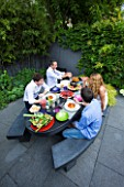 TANIA LAURIE  LONDON. TANIA AND FAMILY SIT DOWN TO LUNCH IN THEIR CONTEMPORARY GARDEN DESIGNED BY CHARLOTTE ROWE