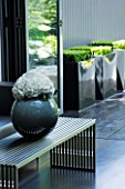 TANIA LAURIE  LONDON. CONTEMPORARY VASE AND LOW LEVEL METAL TABLE IN LIVING AREA LEADING OUT TO PATIO AREA WITH THREE BLACK METAL SQUARE CONTAINERS PLANTED WITH BOX
