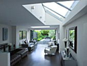 TANIA LAURIE  LONDON. INTERIOR OF LIVING / DINING AREA WITH ROOFLIGHT LEADING OUT ONTO CONTEMPORARY GARDEN DESIGNED BY CHARLOTTE ROWE