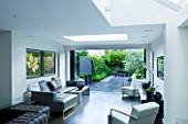 TANIA LAURIE  LONDON. INTERIOR OF LIVIN AREA LEADING OUT ONTO PATIO AND CONTEMPORARY GARDEN DESIGNED BY CHARLOTTE ROWE