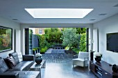 TANIA LAURIE  LONDON. INTERIOR OF LIVING AREA LEADING OUT ONTO PATIO AND CONTEMPORARY GARDEN DESIGNED BY CHARLOTTE ROWE