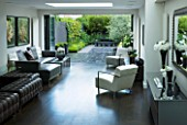 TANIA LAURIE  LONDON. INTERIOR OF LIVING / DINING AREA LEADING OUT ONTO PATIO AND CONTEMPORARY GARDEN DESIGNED BY CHARLOTTE ROWE