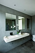 TANIA LAURIE  LONDON. STYLISH  CONTEMPORARY BATHROOM WITH WALL MOUNTED DOUBLE STONE SINK  GREY SLATE WALLS  MIRRORS AND WHITE ORCHID