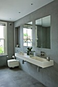 TANIA LAURIE  LONDON. WALL MOUNTED DOUBLE STONE SINK IN GREY SLATE TILED BATHROOM WITH MIRRORS